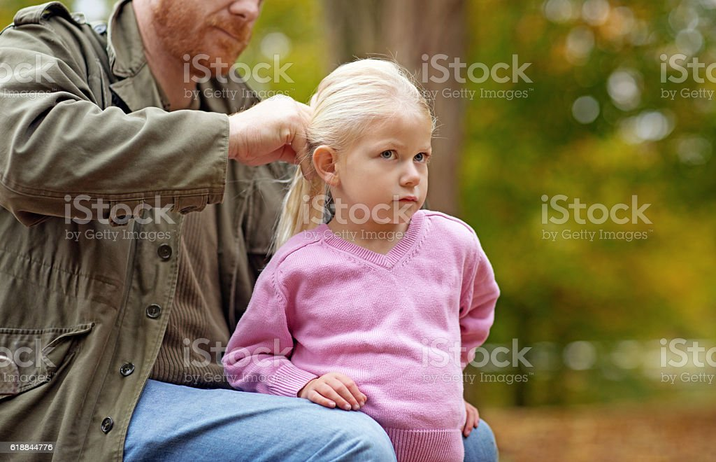 Single father brushing and fixing daughter\'s hair in autumnal...