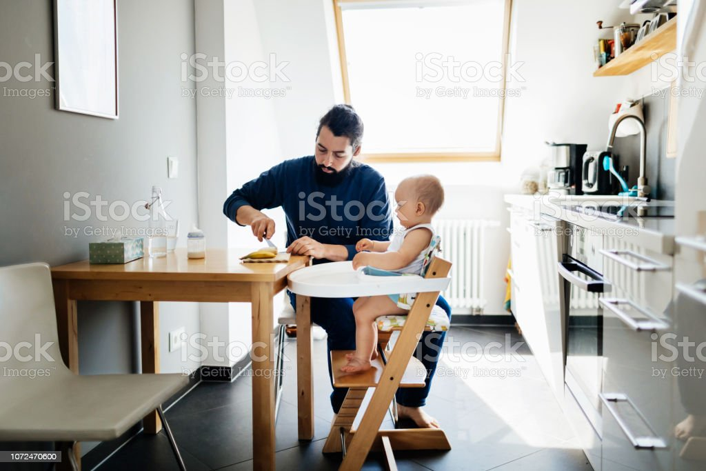 A single father feeding his baby in a high chair, while at home...