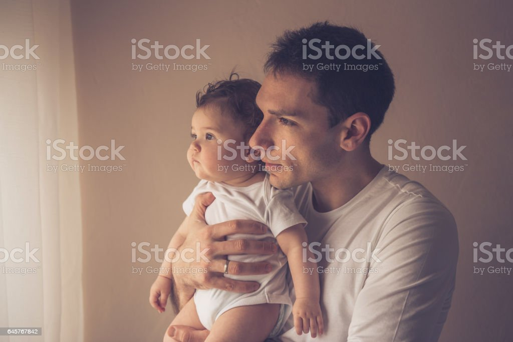 Single father holding baby boy in his arms and looking through...