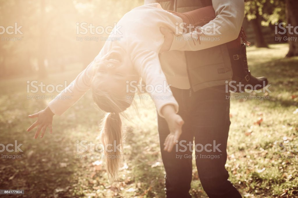 Single father in park with daughter. holding little girl and rotate in circle. royalty-free stock photo