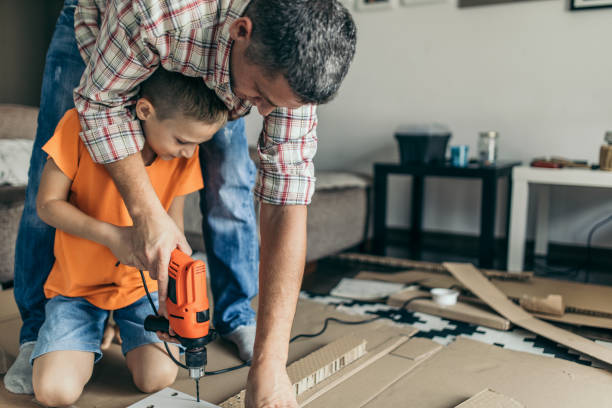 Single father is assembling furniture with his kids stock photo
