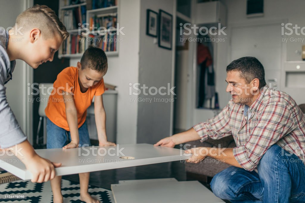 Single father is assembling furniture with his kids