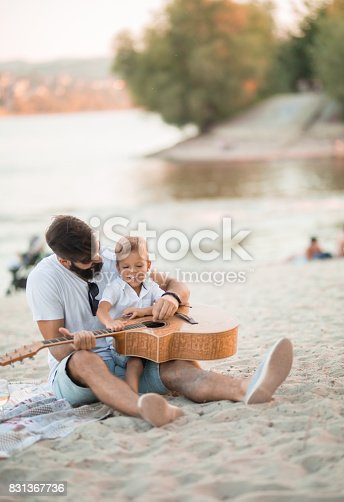 istock Single father is having fun at the beach with his son 831367736