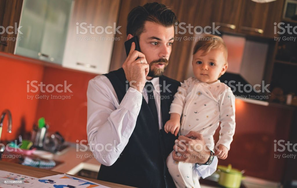 Single businessman father holding baby boy while talking on the phone...