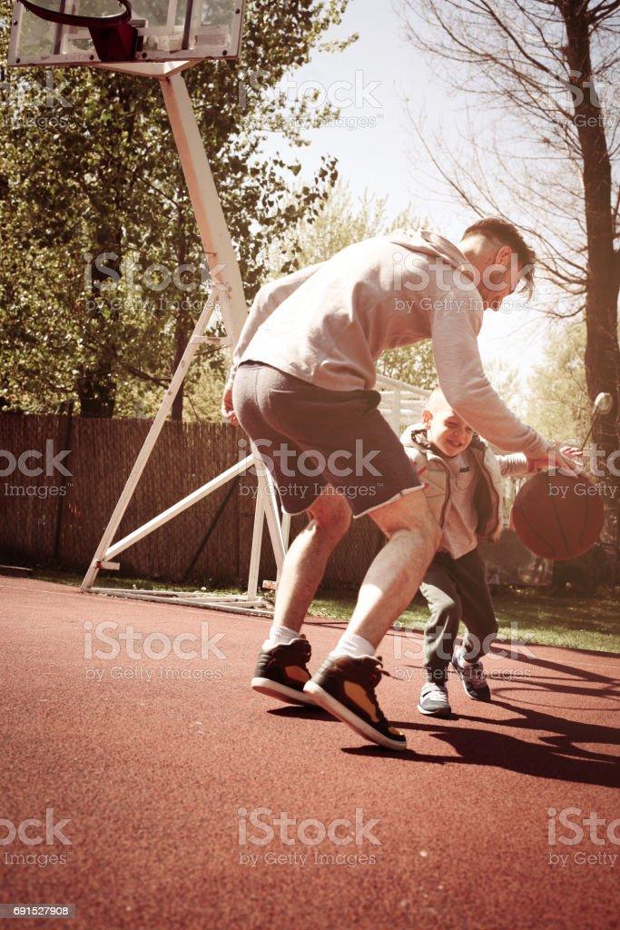 Single father playing basketball together on the basketball court. stock photo