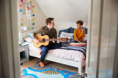 istock Single Father Playing Guitar With Son Who Drums On Cushion In Bedroom 1154943743