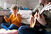istock Single Father Playing Guitar With Son Who Drums On Cushion In Bedroom 1154943999