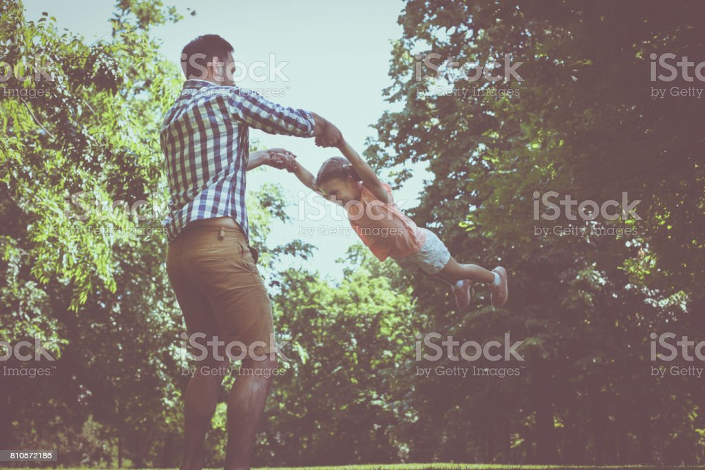 Single father playing in the meadow with daughter. Enjoying in summer...