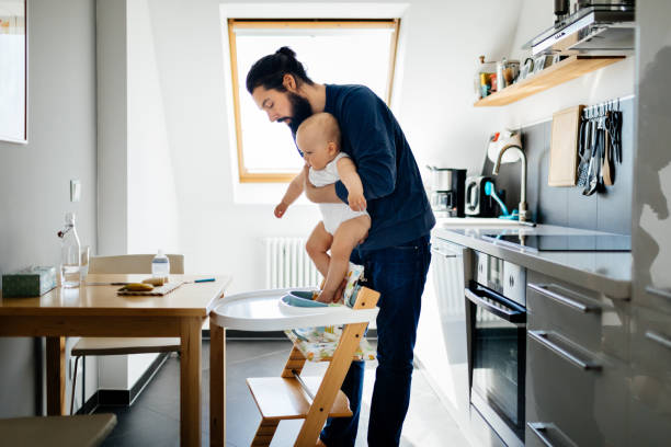 Single Father Putting Baby In High Chair A single father putting his baby in a high chair, getting ready for lunch. man bun stock pictures, royalty-free photos & images