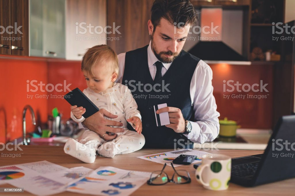 Single businessman father holding baby boy and a credit card while...