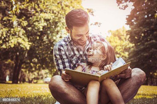 istock Single father sitting on grass with little daughter and reading book story. Little girl sitting on father lap. 692848374