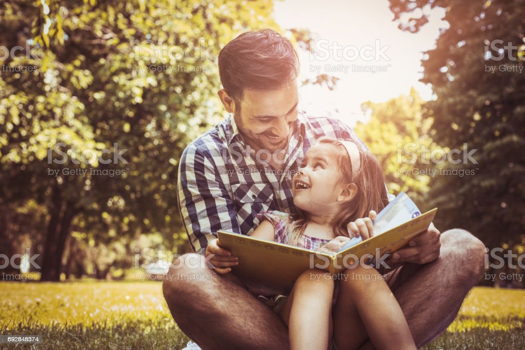 Single father sitting on grass with little daughter and reading book story. Little girl sitting on father lap. stock photo