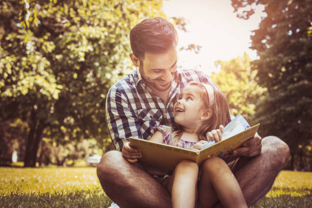 single father sitting on grass with little daughter and reading book story. little girl sitting on father lap. - father and daughter stock photos and pictures