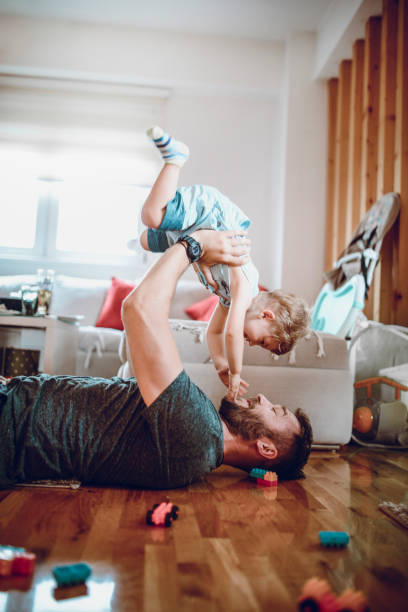 Single Father Spending Quality Time With Baby Son In Living Room stock photo