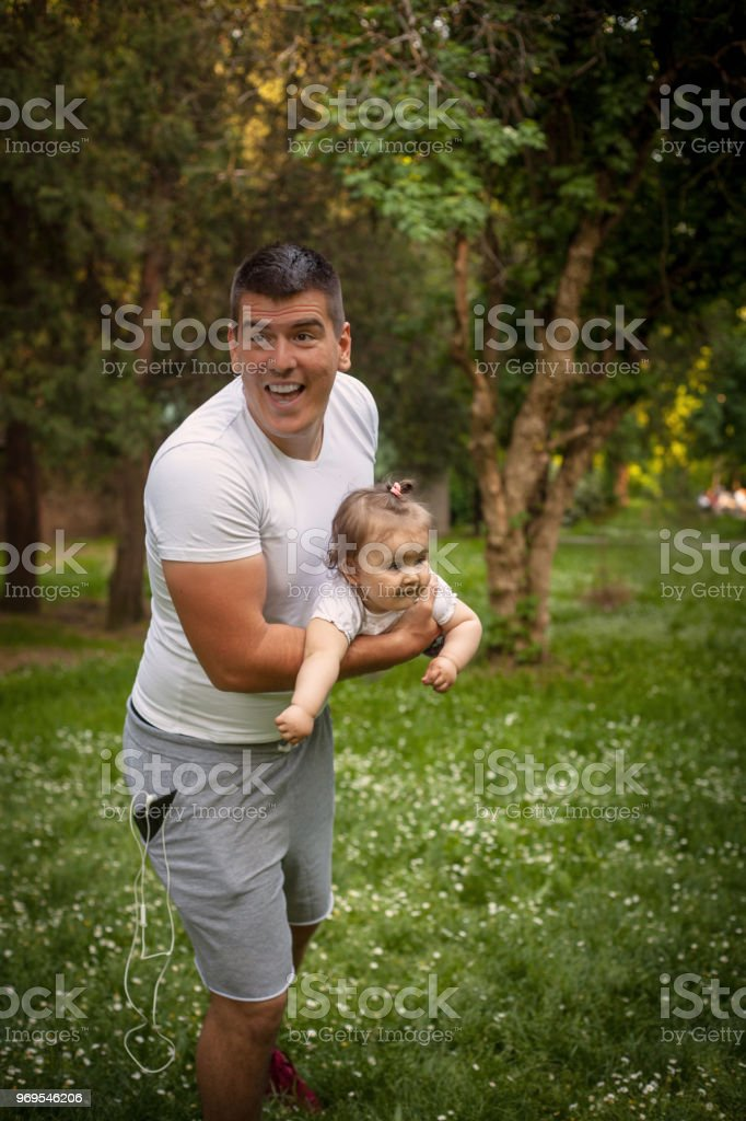 Father and daughter playing in park.