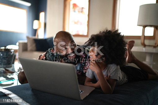 Single father wacthing movie on a laptop with his daughter