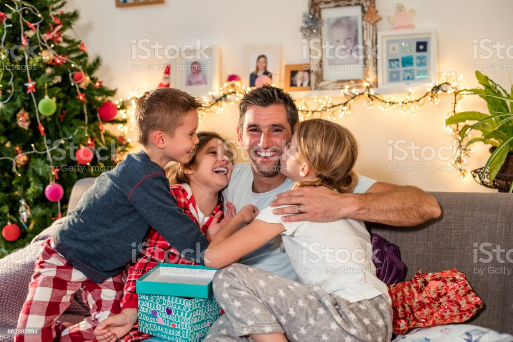 A single dad on Christmas morning sitting on a sofa with his three...
