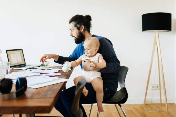 Single Father Working While Holding Baby A single father working at his desk at home while holding his baby son. man bun stock pictures, royalty-free photos & images