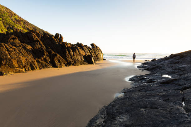Single Figure in the Morning Light on a Deserted Beach stock photo