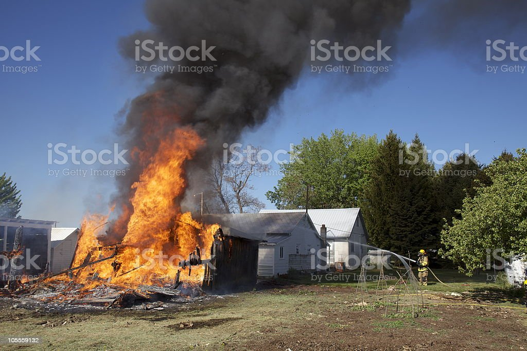 Single firefighter fighting a barn on fire alone. stock photo