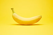 istock Single fresh raw clean isolated one alone horizontally oriented yellow banana on the bright solid yellow fond background 1266340637