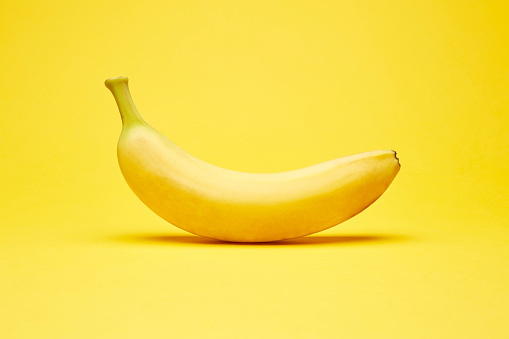 Single fresh raw clean isolated one alone horizontally oriented yellow banana on the bright solid yellow fond background
