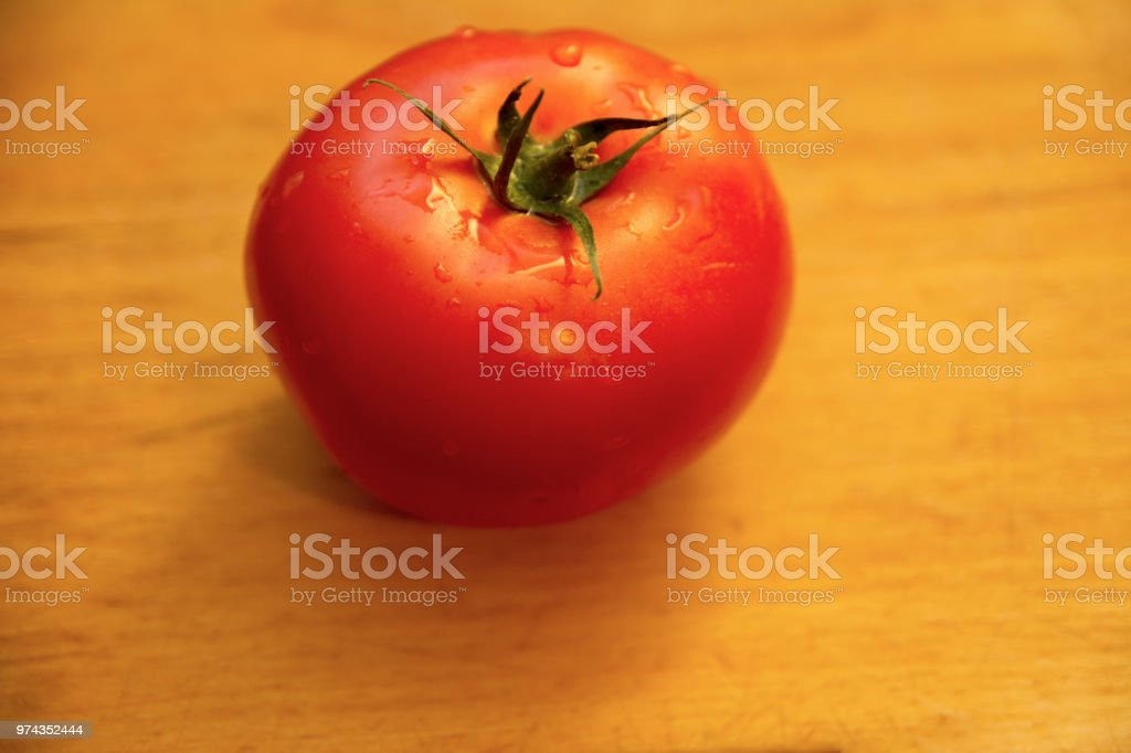 Single Fresh tomatoe on wooden table for cooking stock photo
