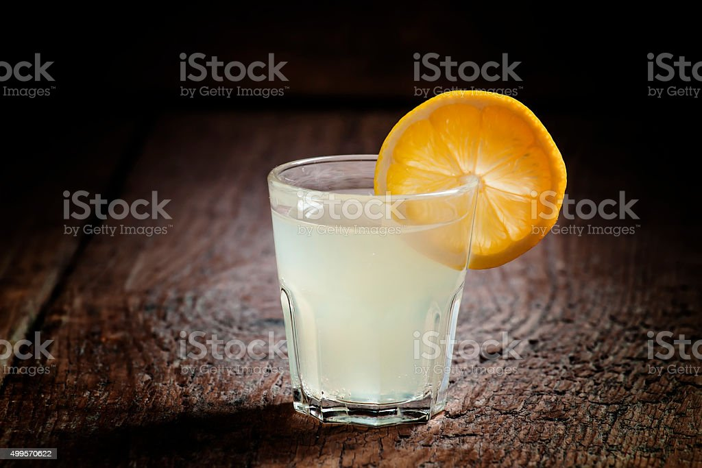 Single glass of vodka with lemon and lemon slice stock photo