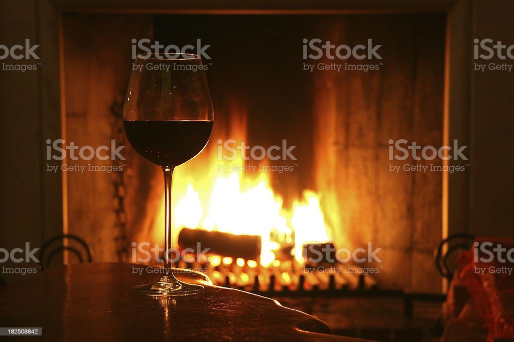 A single glass of wine by a fireplace stock photo