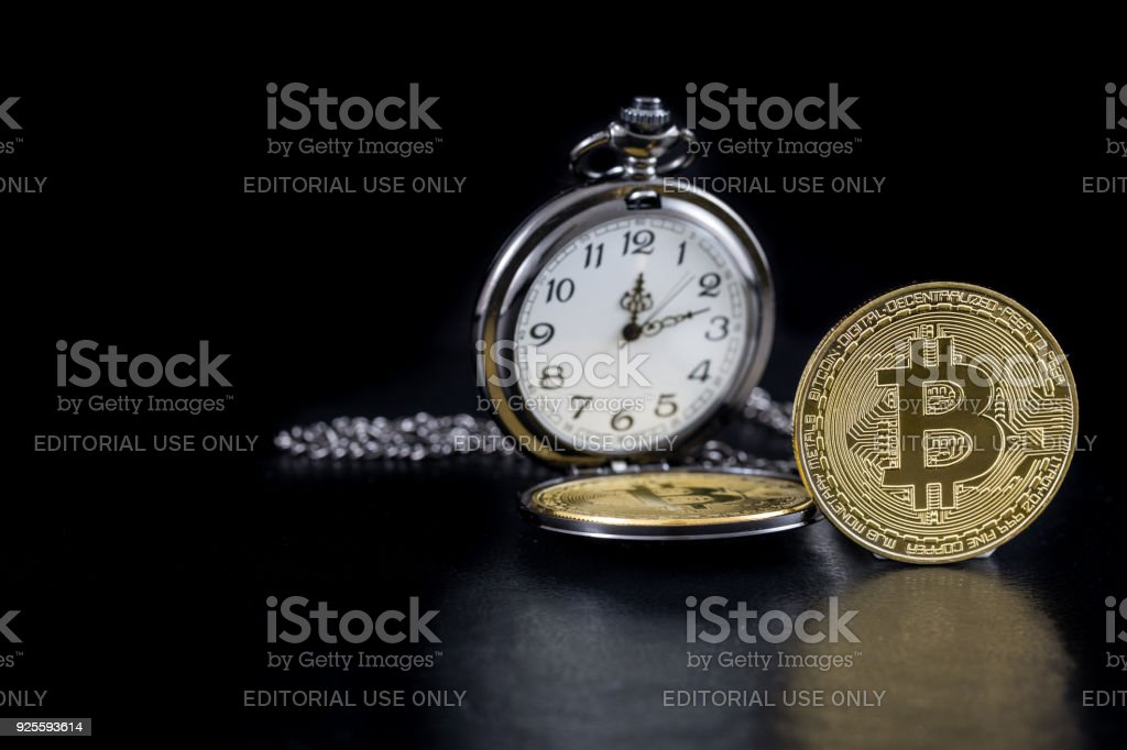 Single golden bitcoin and pocket watch on black background stock photo