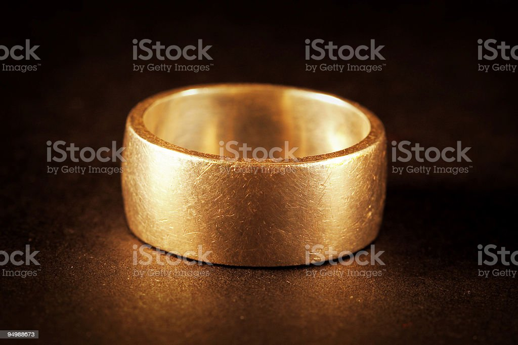 A single golden ring on a brown background stock photo