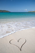Single heart sits invitingly in the sand on the shore of a bright blue tropical sea
