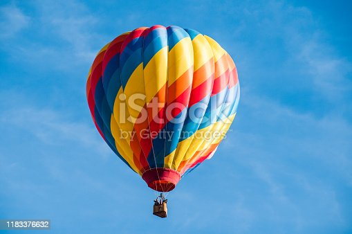 Yellow, red and blue hot air balloon flying overhead in a clear blue sky.