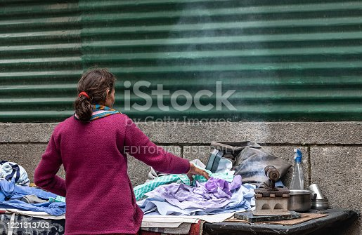 A single Indian woman working on streets ironing clothes using a coal powered old iron. A small business owner living on daily earning.