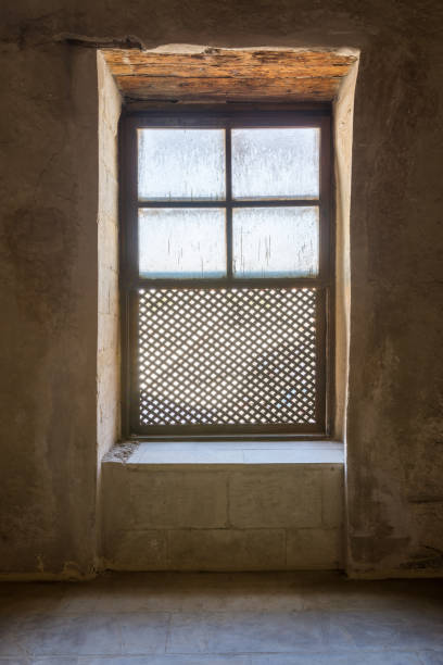 Single Interleaved grunge wooden ornate window - Mashrabiya - in stone wall at abandoned building stock photo