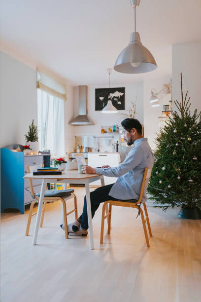 Single Japanese man does Christmas online shopping at home Young Asian man sitting behind a laptop, buying Christmas presents online. bachelor stock pictures, royalty-free photos & images