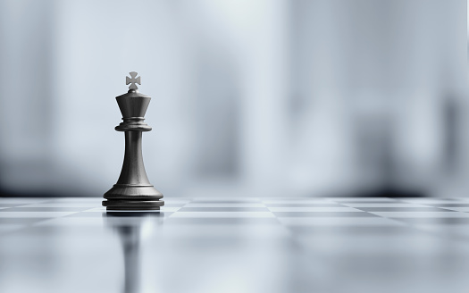 Single king chess piece is standing on black and white chessboard. Horizontal composition with selective focus and copy space. Great use for strategy concepts.