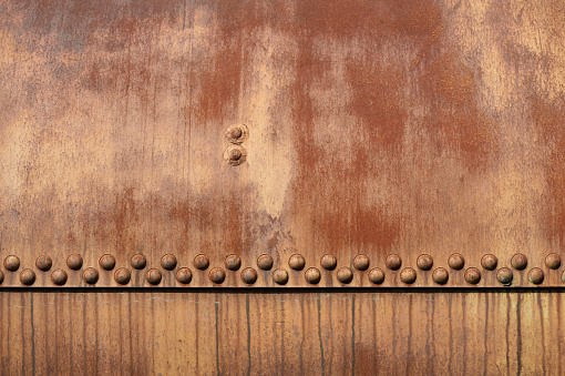 High resolution photograph of a rusty metal surface with rivets.