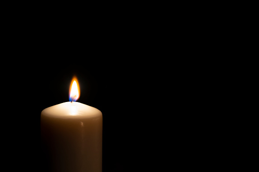 Single lit candle with quite flame in the dark. The composition is at the left of an horizontal frame leaving useful copy space for text and/or logo at the right. High resolution 42Mp studio digital capture taken with Sony A7rii and Sony FE 90mm f2.8 macro G OSS lens