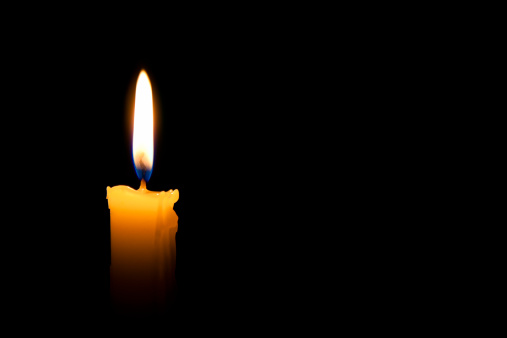 Single lit candle with quite flame on black background