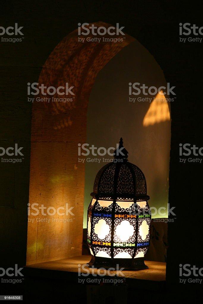 Single lit lantern in a dark room stock photo