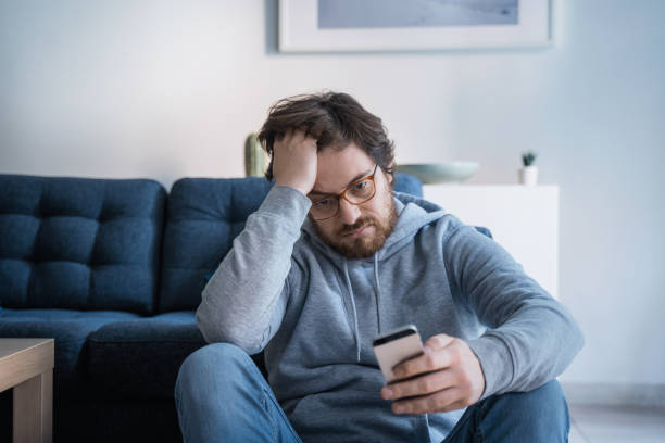 Single lonesome guy checking cell on the couch stock photo