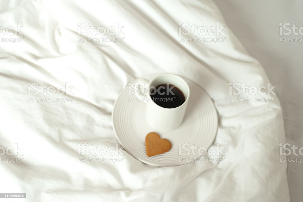Coffee mug and heart shaped cookie on white bed
