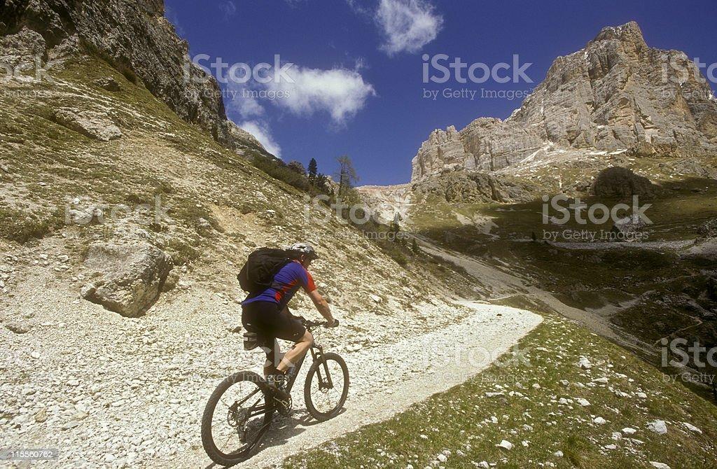 Single male biker rides uphill, Dolomites, Italy royalty-free stock photo