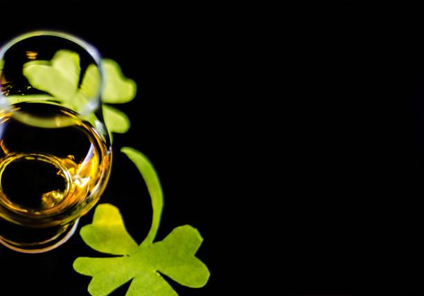 Uísque de malte em uma taça de degustação com decoração para o dia de São Patrício, símbolo do trevo verde para feriado irlandês - foto de acervo
