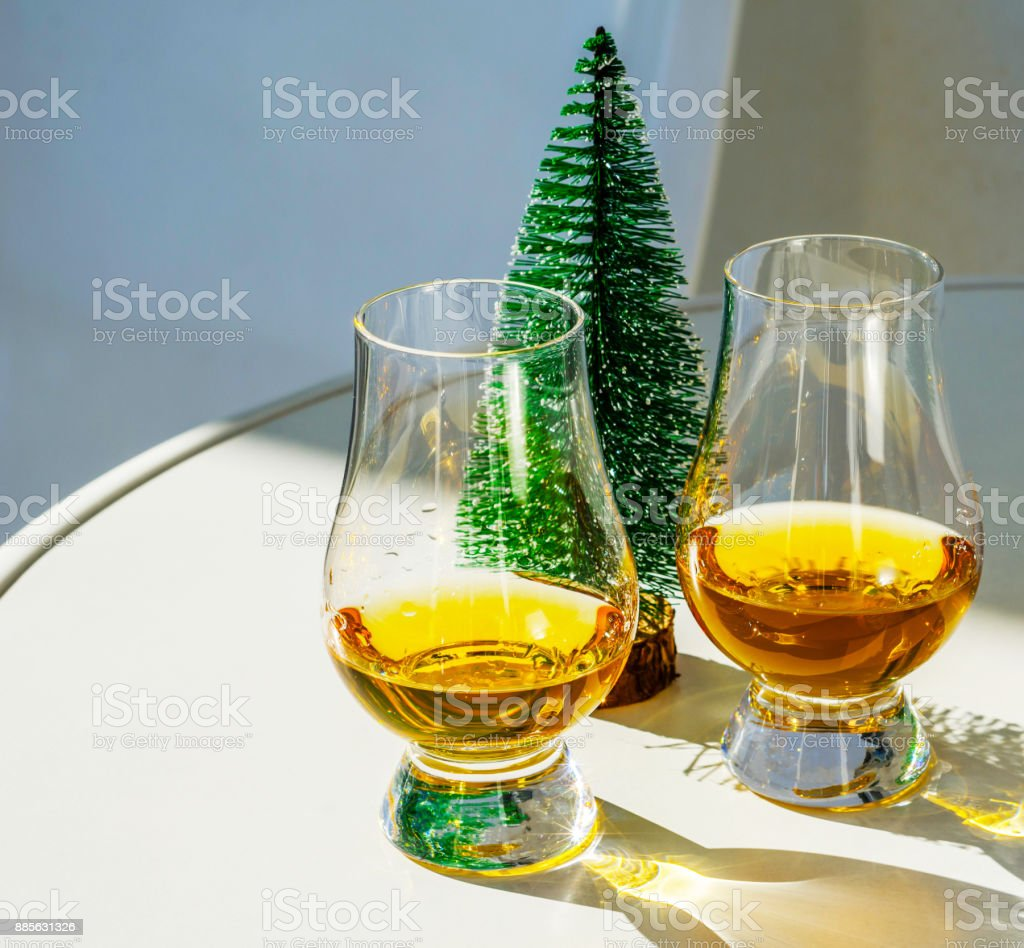single malt whisky  in the glass with decorative Christmas tree, luxurious tasting glass stock photo
