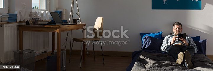 istock Single man in his apartment 486771690
