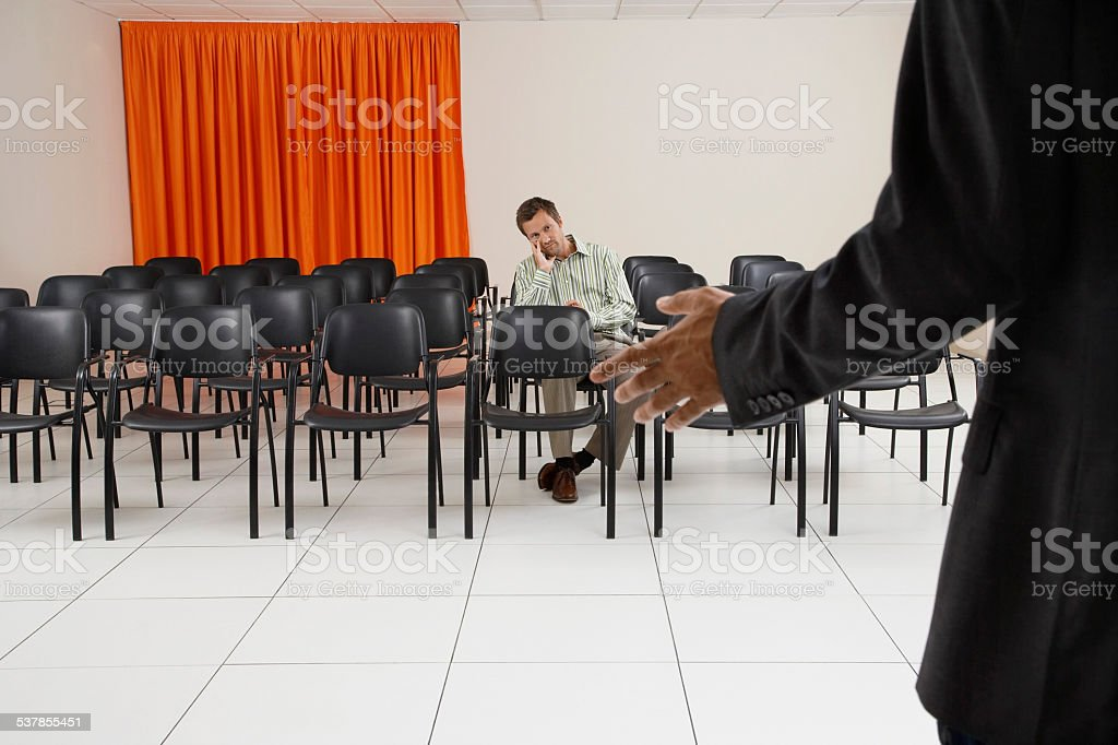 Single man listening to a seminar in conference room stock photo