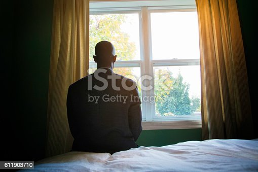 istock SIngle man praying in suit in front of window 611903710