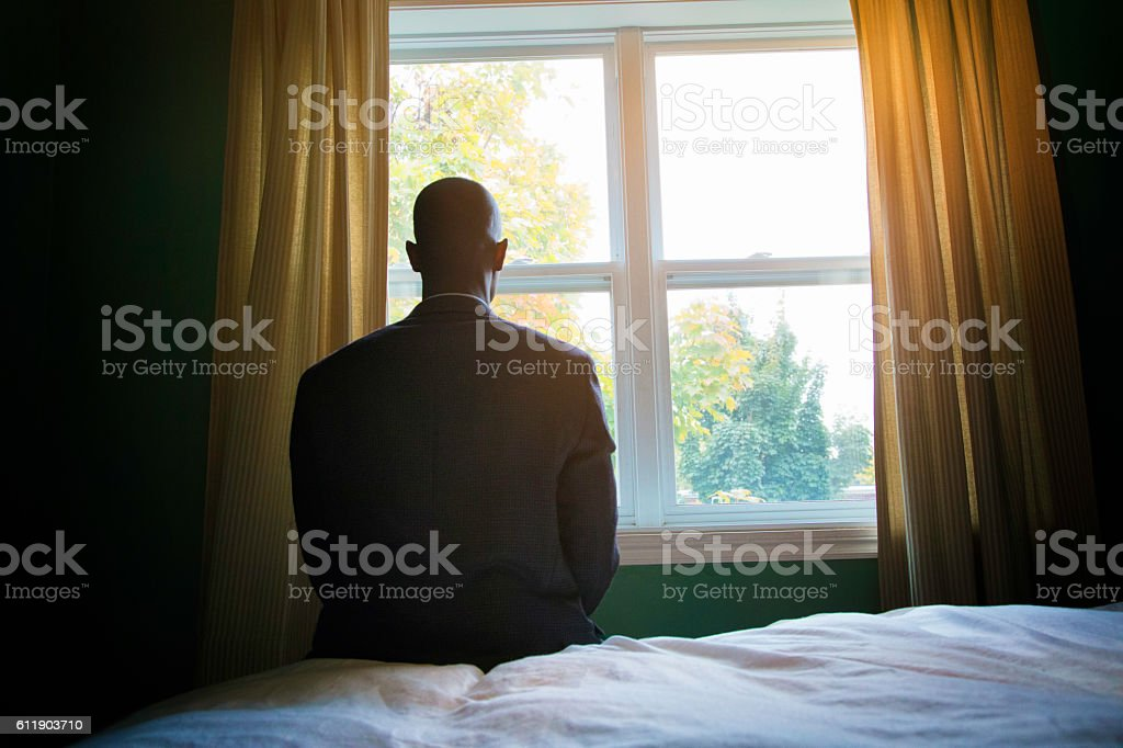 SIngle man praying in suit in front of window stock photo